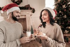 Happy man giving glass with milk. So tasty. Charming girl expressing positivity while looking upwards and holding plate with biscuits royalty free stock photos