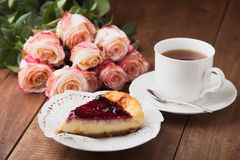 Tasty cheese cake and a cup of hot tea with roses. On wooden table Stock Images