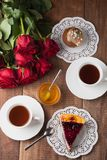 Tasty cheese cake and cupcake with two cup. Tasty cheese cake and cupcake on wooden table with two cup of hot tea with red roses Stock Photography