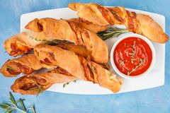 Tasty cheese sticks with bacon, herbs and tomato sauce. Top view