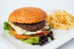 Tasty cheeseburger with fried potatoes, isolated Stock Photography