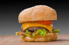 Tasty cheeseburger with lettuce, beef, double cheese and ketchup. Royalty Free Stock Images