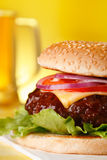 Tasty cheeseburger with pint of beer on background Royalty Free Stock Photos