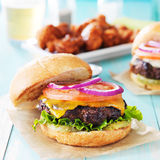 Tasty cheeseburgers with wings and beer Stock Photo