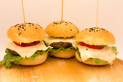 Tasty cheeseburgers on a wooden board. Tasty cheeseburgers with tomatoes, cucumbers and green salad on a wooden board Royalty Free Stock Images