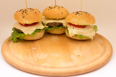 Tasty cheeseburgers on a wooden board. Tasty cheeseburgers with tomatoes, cucumbers and green salad on a wooden board Stock Photography