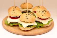 Tasty cheeseburgers on a wooden board. Tasty cheeseburgers with tomatoes, cucumbers and green salad on a wooden board Royalty Free Stock Photo
