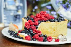Tasty cheesecake with fresh blueberries and raspberries on a wooden background.  Royalty Free Stock Images