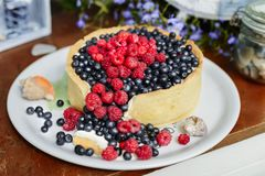 Tasty cheesecake with fresh blueberries and raspberries on a wooden background.  Royalty Free Stock Photo