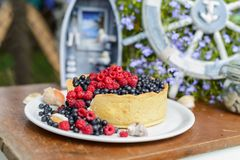 Tasty cheesecake with fresh blueberries and raspberries on a wooden background. Candy bar Royalty Free Stock Image