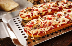 Tasty cheesy baguettes with mushroom and tomato Stock Photo