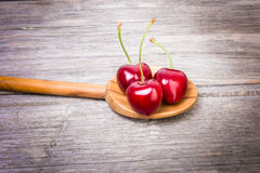 Tasty cherries. Some red cherries on a spoon against wooden background Royalty Free Stock Photo