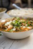 Tasty chicken butter masala on wooden table Stock Image