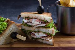 Chicken club sandwich. Tasty chicken club sandwich with fries on wooden table royalty free stock images