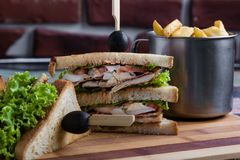 Chicken club sandwich. Tasty chicken club sandwich with fries on wooden table royalty free stock image