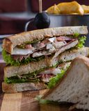 Chicken club sandwich. Tasty chicken club sandwich with fries on wooden table royalty free stock photography