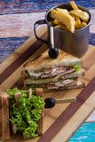 Chicken club sandwich. Tasty chicken club sandwich with fries on wooden table stock photo