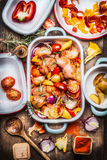 Tasty chicken with colorful vegetables and red sweet paprika in casserole, preparation on rustic wooden background and cutting coo Royalty Free Stock Images