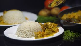 Tasty chicken curry, Indian dish with steamed rice. Chef adding chicken curry to the steamed rice, plate on the black stock video