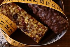 Free Tasty Chocolate Bars And Peanut Brittle With A Measuring Tape Royalty Free Stock Photo - 56148145