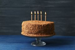 Tasty chocolate cake with candles on wooden wall. Background Royalty Free Stock Photos