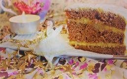 Tasty chocolate cake. The magic of each piece of cake. A piece of chocolate cake on a plate, sprinkled with powdered sugar close to the ceramic figurine Fairy Stock Photos