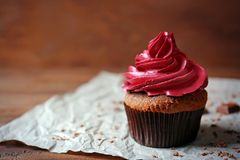 Tasty chocolate cupcake and paper napkin. On wooden table royalty free stock images