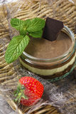 Tasty chocolate dessert with strawberries and mint on a wicker support Stock Image
