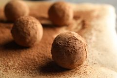 Tasty chocolate truffles on parchment paper. Closeup stock photography