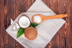 Tasty coconut cracked in half and a whole coco with green leaves on a wooden background. A spoon of coco chips. Tropical fruits. Royalty Free Stock Photos