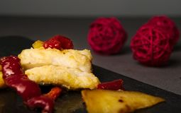 Cod and red peppers. Tasty cod and red peppers over slate board and gray textile with red decoration balls at the back Stock Photo