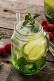 Tasty cold fresh drink lemonade with lemon, mint, raspberry, ice. And lime in glass on wooden table. Closeup Stock Image