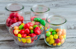 Tasty colorful candies in glass bowl and jars. Close-up of multicolored candies in glass bowl and jars on wooden table Royalty Free Stock Image