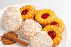 Tasty colorful cookies on white plate. Tasty crisp cookies with jam, gingerbread cookies and some cinnamon powder with cinnamon roll on white plate Stock Photography