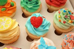 Tasty colorful cupcakes in open box. Tasty colorful cupcakes in open paper box Royalty Free Stock Image