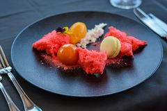 Red desert with macaron on black plate in restaurant. royalty free stock photos