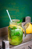 Tasty colorful drink with cold green tea, mint and lemon in a glass jar on a vintage background Royalty Free Stock Images