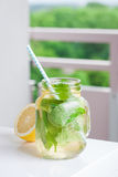 Tasty colorful drink with cold green tea, mint and lemon in a glass jar on a white kitchen background Stock Photo