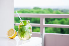 Tasty colorful drink with cold green tea, mint and lemon in a glass jar on a white kitchen background Stock Images