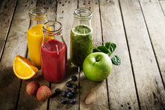 Tasty colorful fresh homemade smoothies in glass jars on wooden Royalty Free Stock Images