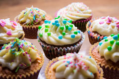 Tasty colorful muffins with butter cream Stock Images