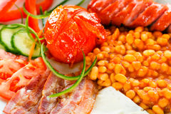Tasty continental breakfest. A closeup of continental breakfast containing sausages, bean truck, bacon, fresh vegetables, fried eggs and bread royalty free stock photo