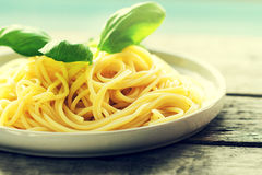 Tasty cooked colorful spaghetti pasta with fresh basil on plate Royalty Free Stock Image