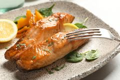 Tasty cooked salmon with lemon on plate. Closeup Stock Image