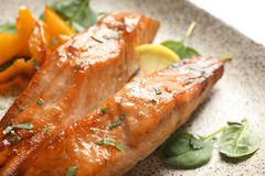 Tasty cooked salmon with lemon on plate. Closeup Royalty Free Stock Photos