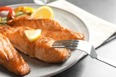 Tasty cooked salmon with lemon on plate. Closeup Stock Images