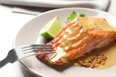 Tasty cooked salmon with mustard on plate. Closeup Royalty Free Stock Photos