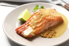 Tasty cooked salmon with mustard on plate. Closeup royalty free stock image