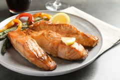 Tasty cooked salmon with vegetables on plate,. Closeup Stock Photos
