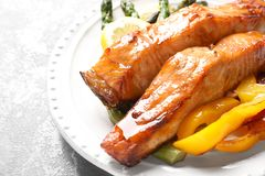 Tasty cooked salmon with vegetables on plate,. Closeup Stock Photo